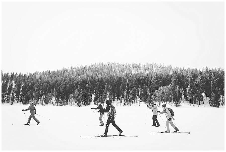 a group of cross country skiers glide across a frozen lake in Levi Lapland by Wild Connections Photography