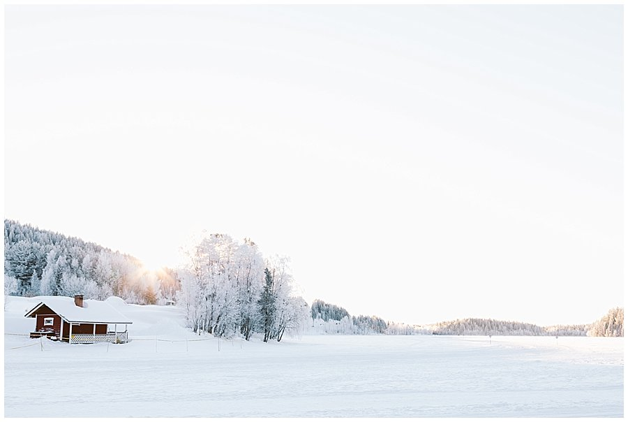 A red wooden cabin stands on the edge of a frozen lake in Levi Finland by Wild Connections Photography