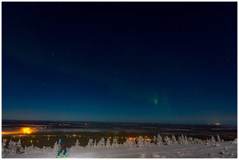 Aurora Borealis Ski Tour the lights show faintly in the sky in Levi Finland by Wild Connections Photography