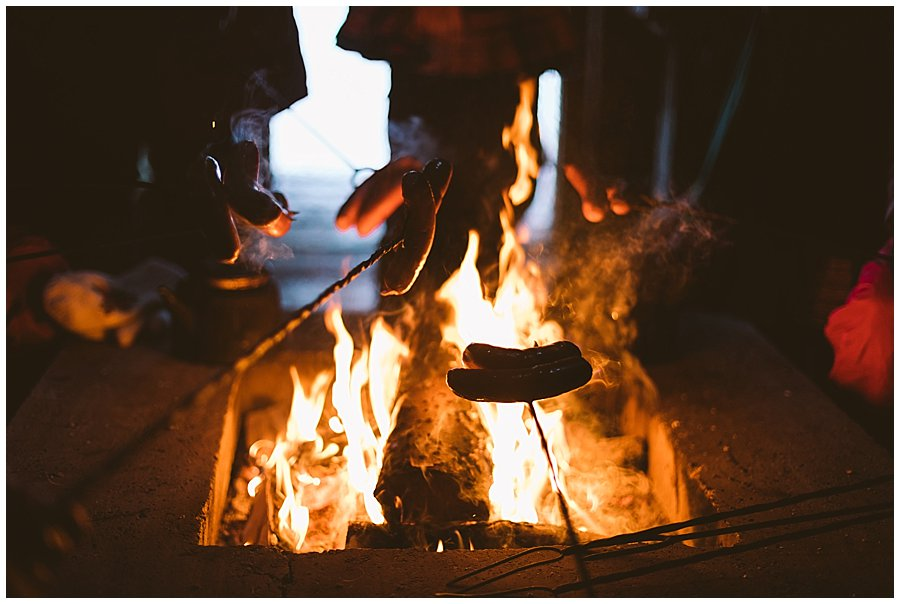 People cook sausages over an open fire in Levi Finland by Wild Connections Photography