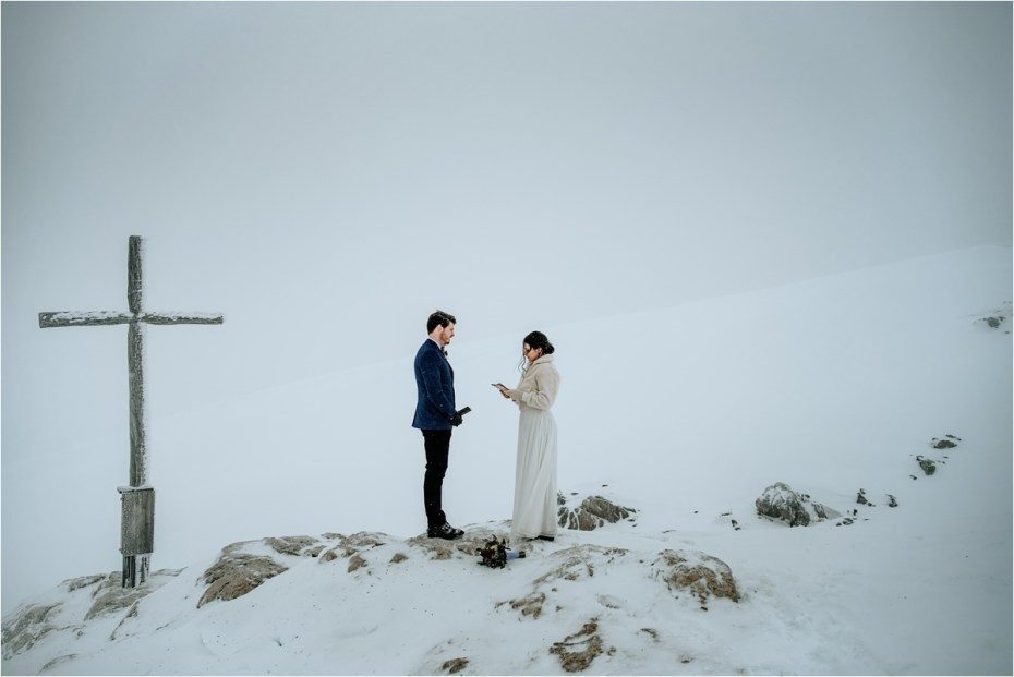 Bride and groom read their wedding vows on the top of a mountain in a snowstorm in Austria. Photos by Wild Connections Photography