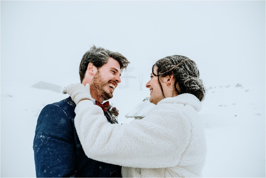 Bride and groom embrace, covered in snow, after their outdoor winter elopement ceremony in Austria. Photos by Wild Connections Photography