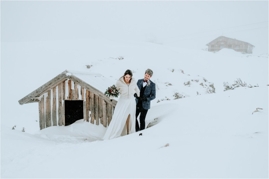 Bride and groom walk through deep snow on their wedding day in the Austrian Alps. Photos by Wild Connections Photography