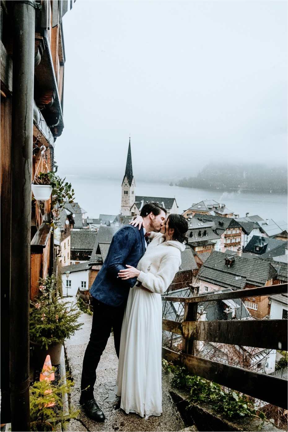 Bride and groom kiss on the steps above Hallstatt. Photos by Wild Connections Photography