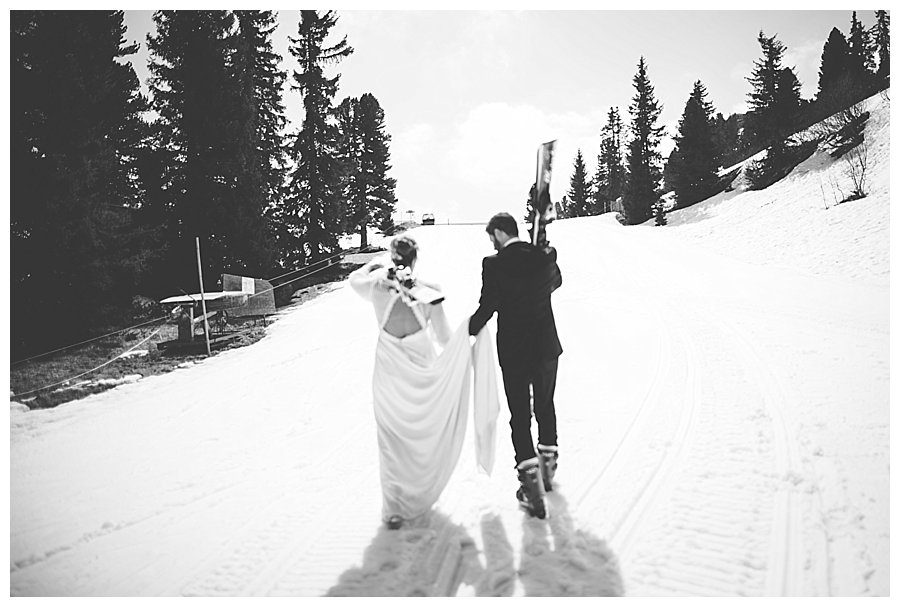 Bride and groom walking up a ski slope