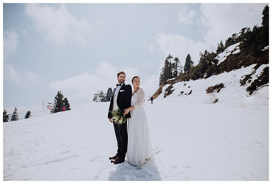 Winter Wedding Austria bride and groom stand on a ski slope while skiers ski past them by wild connections photography