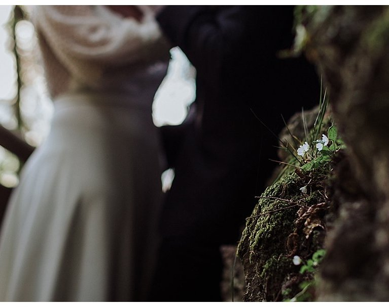Couple leans against some rocks for their adventure wedding in Austria by Wild Connections Photography
