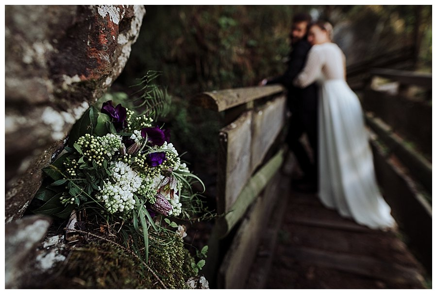 Close up of a bride's bouquet with bride and groom embracing in the distance on a wooden bridge