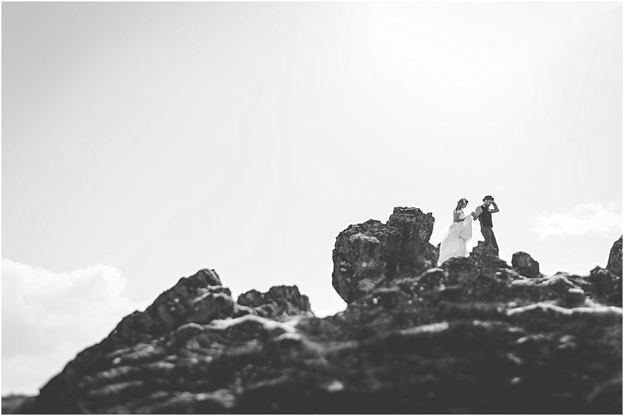 Bride and groom walking over rocks in Thingvellir Iceland