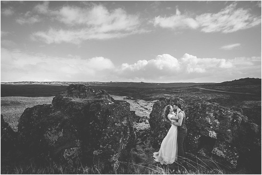 Thingvellir Iceland bride and groom kissing standing amongst rocks