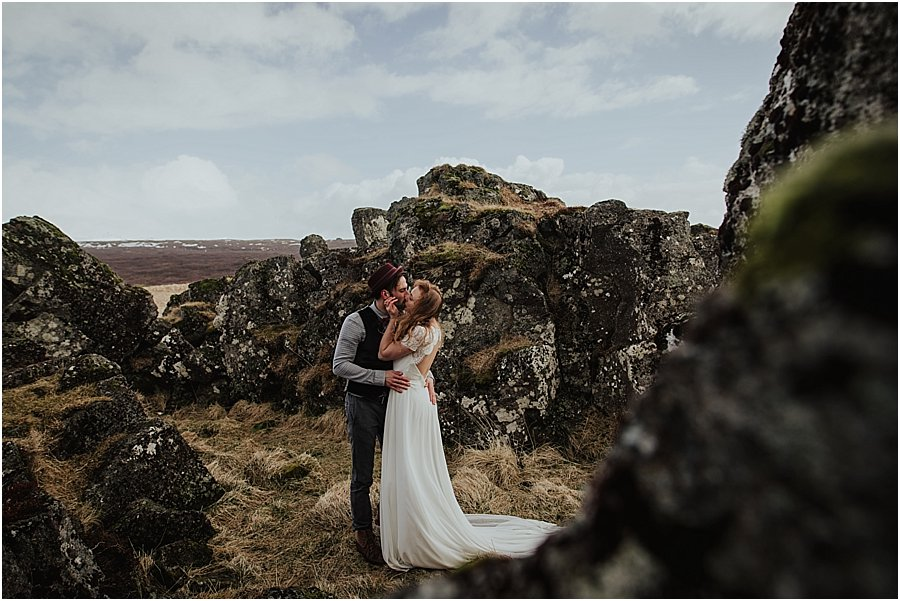 Thingvellir Wedding Photographer bride and groom embrace and kiss amongst large rock formations covered in moss by Wild Connections Photography