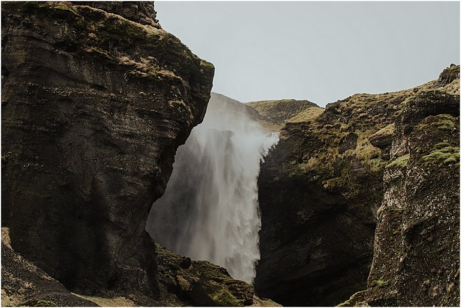 View of a large waterfall from behind the rocks