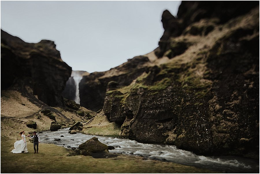 Adventure wedding Bride and groom walk away from a waterfall with the dress blowing in the wind in Iceland by Wild Connections Photography