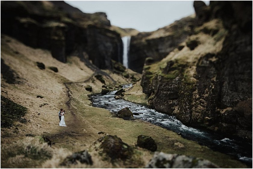 Iceland wedding Bride and groom standing and kissing as part of a wide landscape picture of a waterfall by Wild Connections Photography