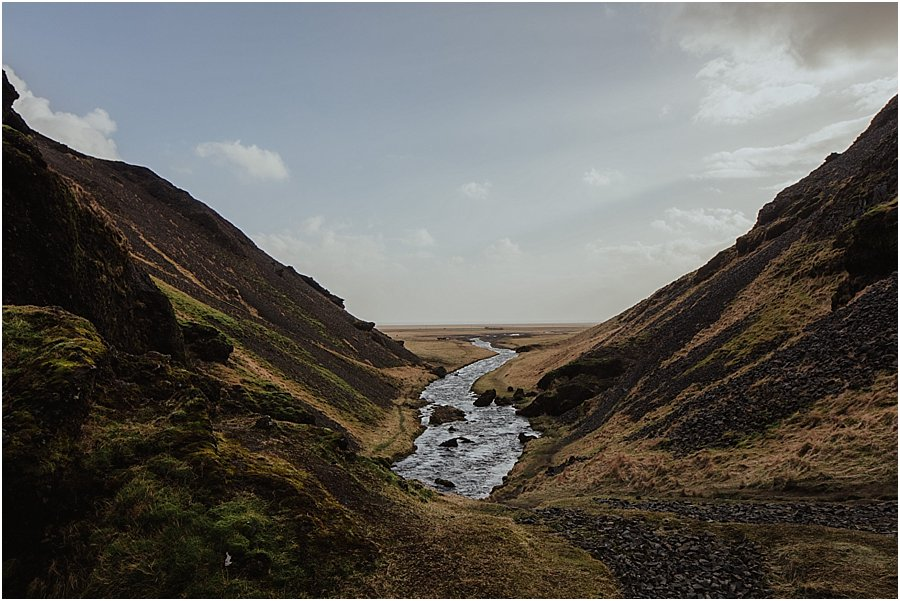 A river valley in Iceland with a river flowing out towards the coast
