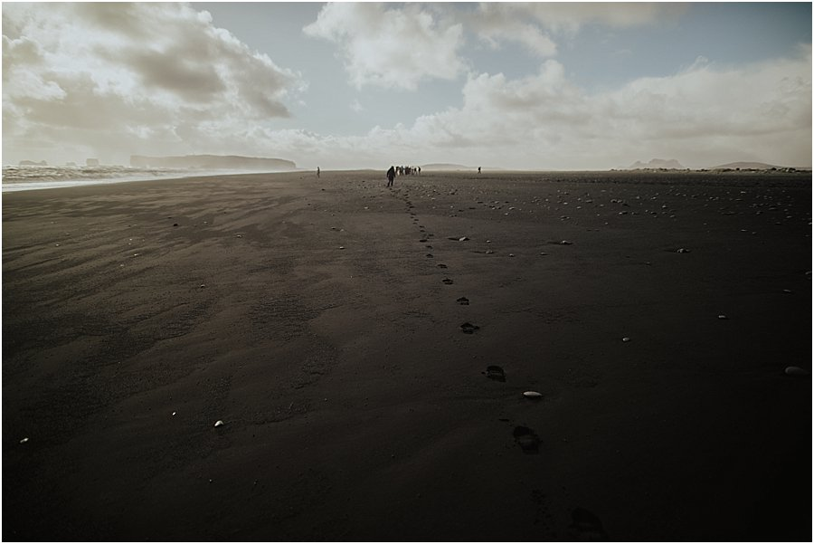 Footprints in the sand on the black beach