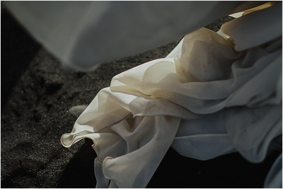 picture of a dirty wedding dress against the black sand