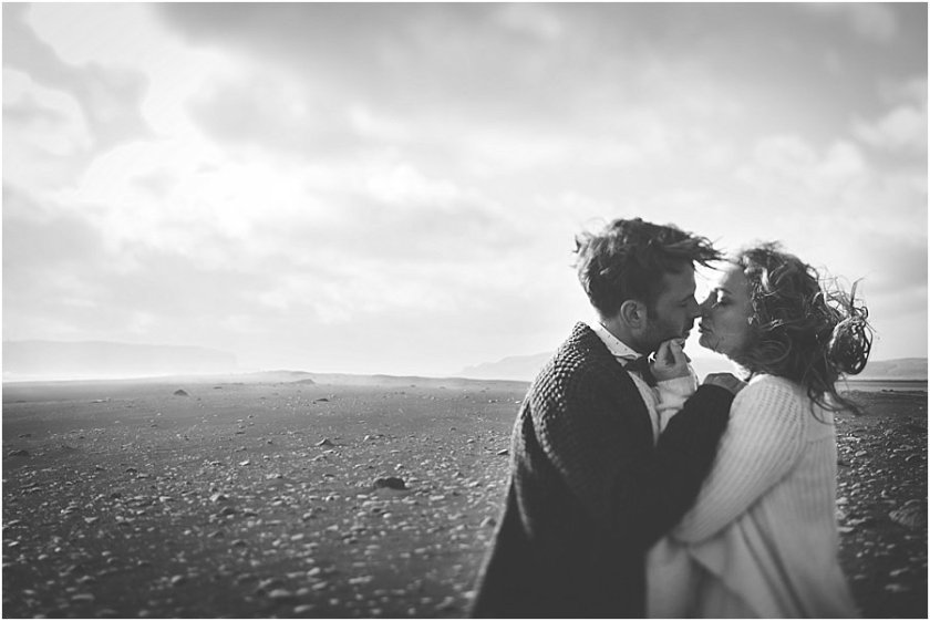 Bride and groom leaning in for a kiss on the black beach