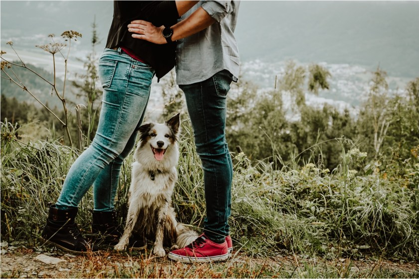 Lucy the dog stands between her owners legs as they kiss by Wild Connections Photography