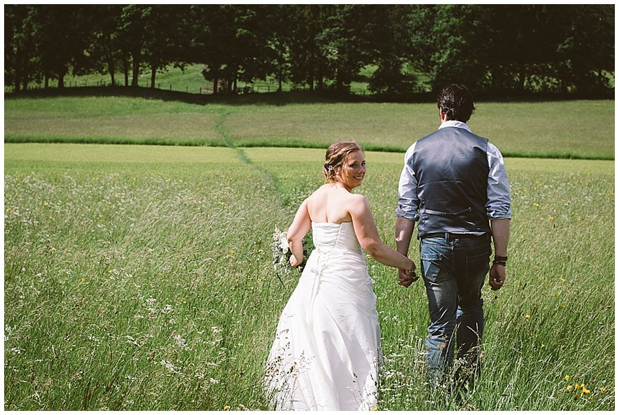 Norfolk Wedding Photographer bride and groom walk hand in hand through long grass by Wild Connections Photography