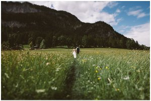 Couple walking through long grass towards mountain after Austrian elopement