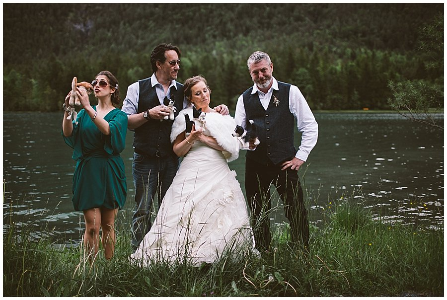 St Johann in Tirol Elopement the party poses with the shelter pups dogs in front of a mountain lake by Wild Connections Photography