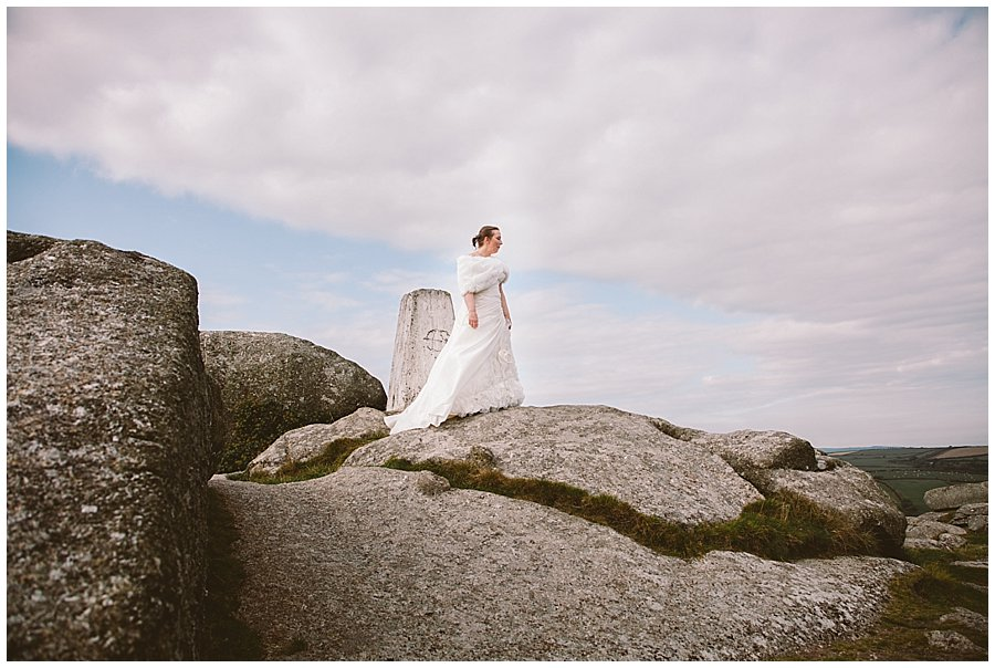 Wedding with Rescue Dogs - Bride in wedding dress standing on rocks looking away from the camera by Wild Connections Photography
