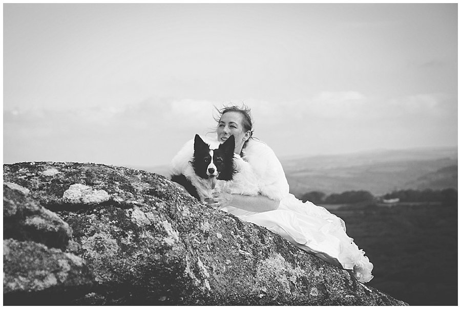 Wedding with Rescue Dogs - Black and white photo of the bride and one of her dogs with its tongue out sitting on the mountain by Wild Connections Photography