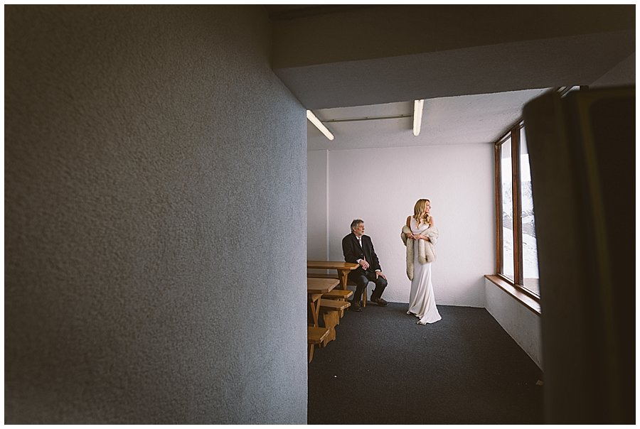 The bride and her father waiting inside in the warm before the outdoor mountain ceremony