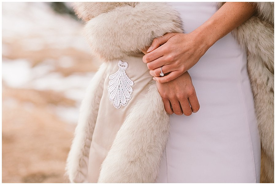 A close up of Steph's engagement ring and her fur wrap
