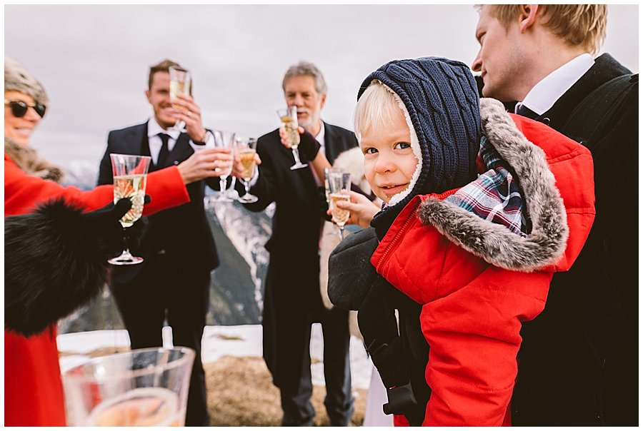 The young nephew looks in to the camera as the adults raise their champagne glasses to toast