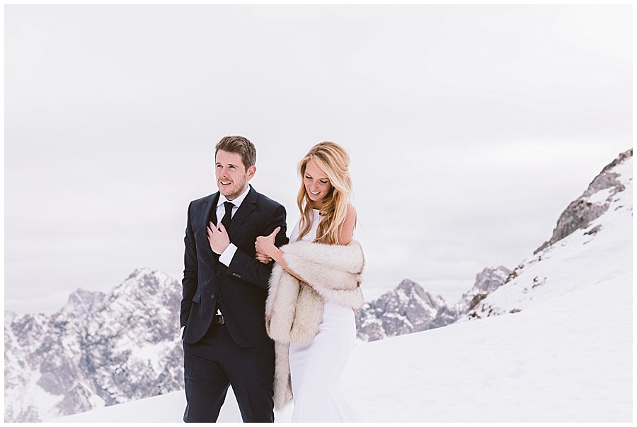Steph and Lee walk arm in arm along the mountain ridge in the snow