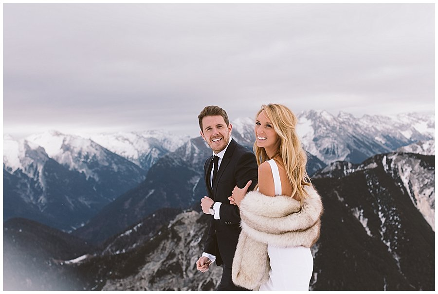 Steph and Leed walk along a mountain ridge and turn back to look at the camera for their Seefeld ski resort wedding by Wild Connections Photography