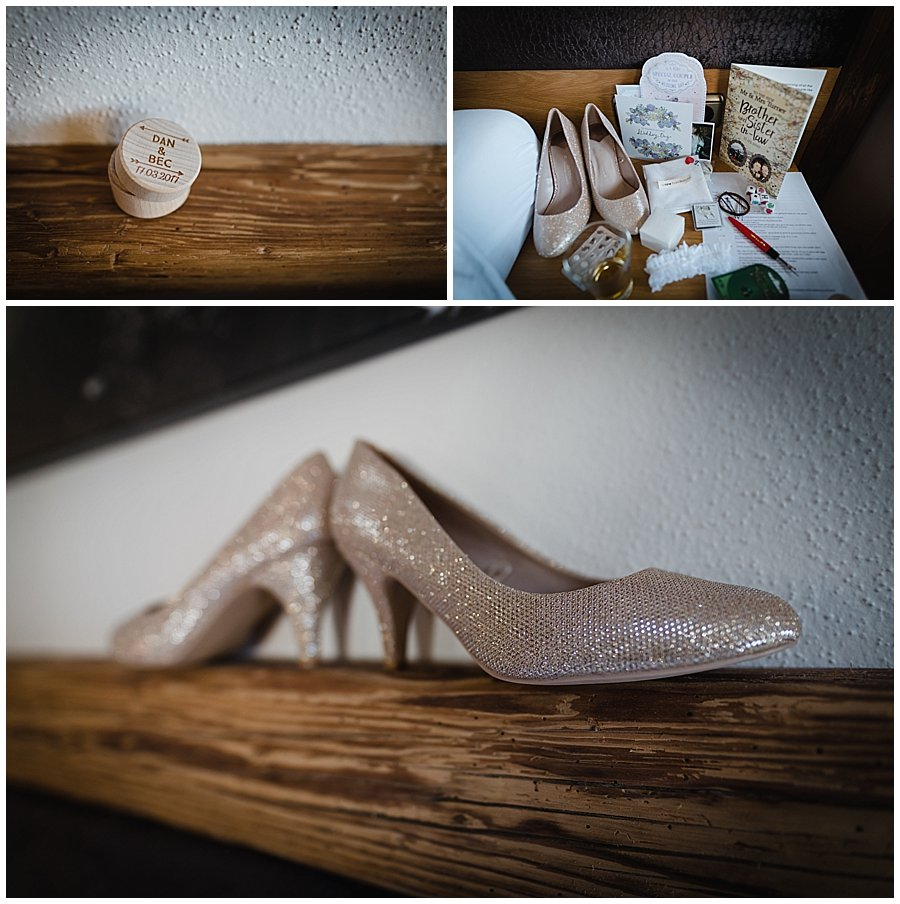 Engraved wooden ring box and glittery shoes on a wooden shelf