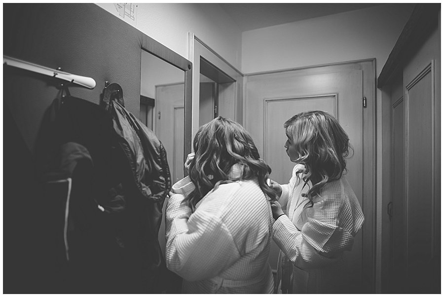 Two bridesmaids look in the mirror in the hallway