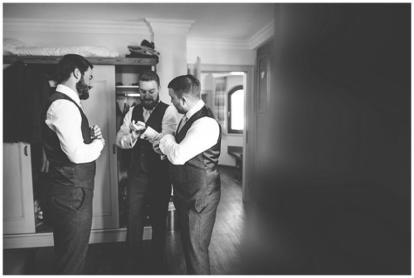 The groom and the groomsmen standing together and talking whilst fixing their cufflinks