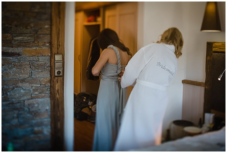Bridesmaid Robyn helps Izzie in to her bridesmaids dress