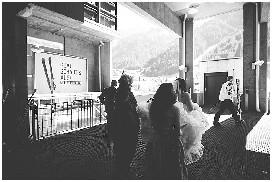 """Bride embarks on cable car with skiers and a sign in the background that say """"looking good"""" in German"""