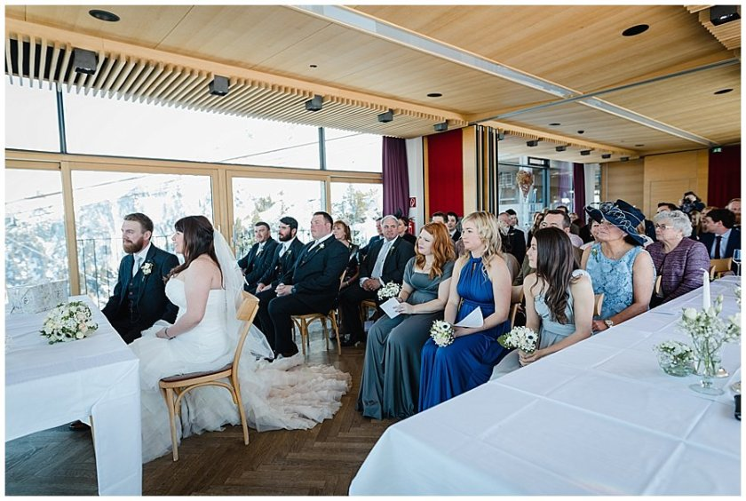 A shot of the wedding ceremony location with the bride and groom at the front and their guests seated in rows