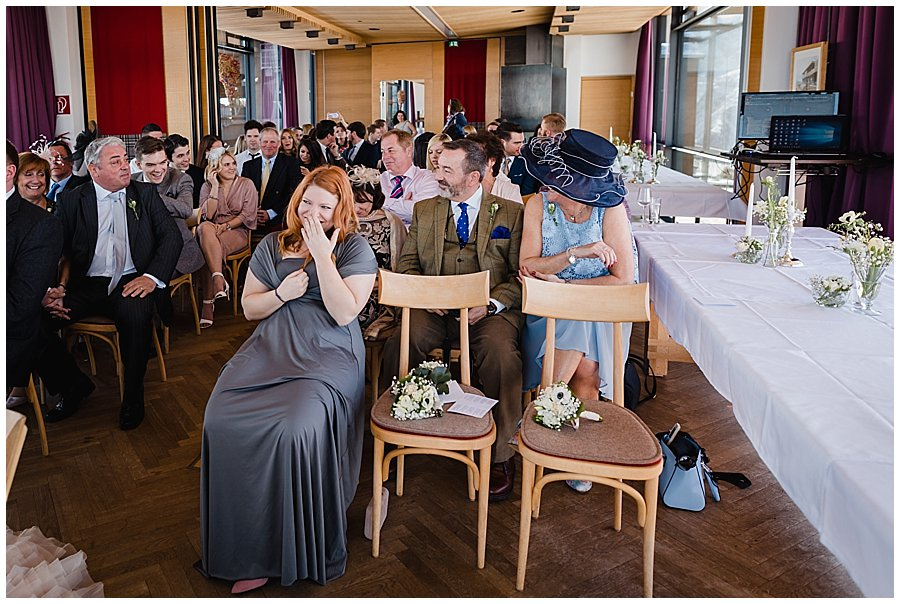 Bridesmaid Rose laughing in her seat as at the back door the other bridesmaid Izzy comes running back in