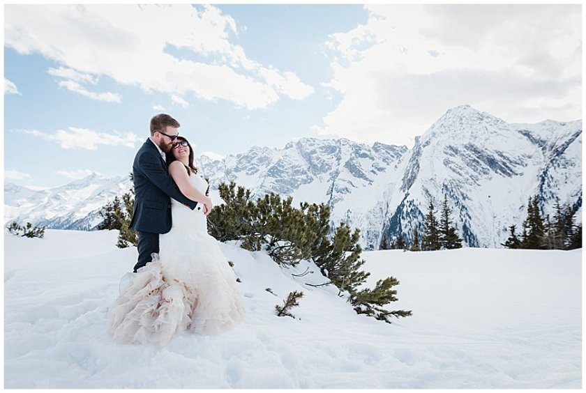 Bride and groom embrace with a mountain backdrop behind them