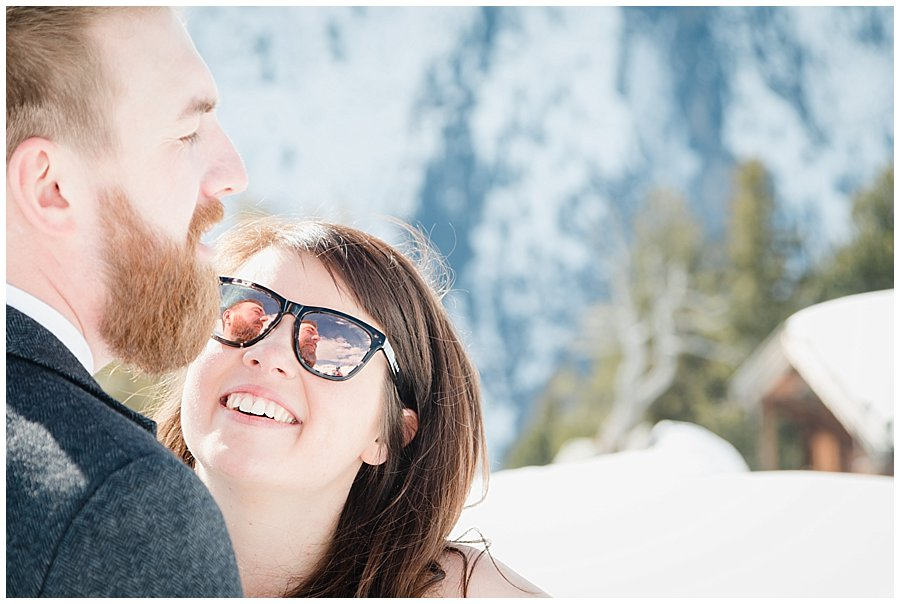 Bride looks at the groom and his face is reflected in her sunglasses