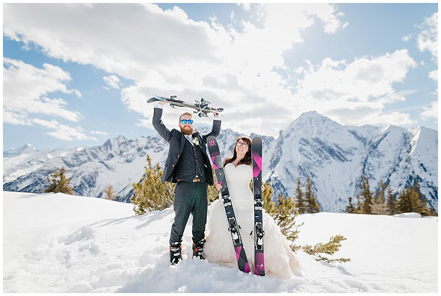 A ski resort wedding with the groom on snowblades and the bride on skis. The bride and groom pose with their skis