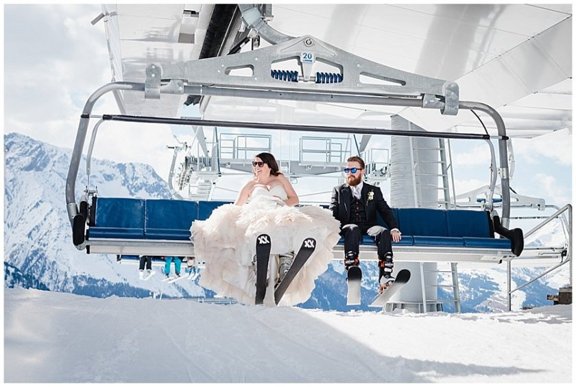 The bride and groom smiling as the reach the top of the chairlift and prepare to disembark
