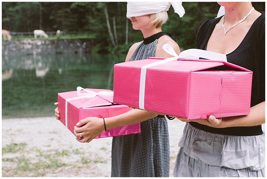 Trash The Dress Photo Shoot Austria - Women stand blindfolded holding pink boxes by Wild Connections Photography