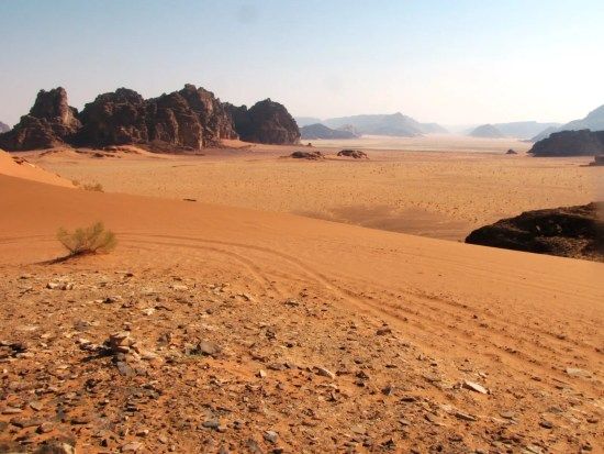 Desert with sand, mountains, and little vegetation