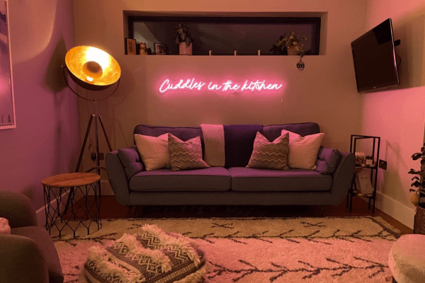 Cuddles in the kitchen pink neon sign above sofa by Wildfire Neon