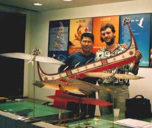 Buteo Huang standing in his studio. On the foreground several kites from the super mini kite series are displayed and the Kite-Flying Dutchman is holding a kite shaped like a Lanyu fishing canoe.