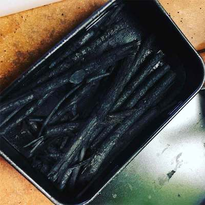 In addition to making bone black, we'll make charcoal sticks. Willow sticks, freshly charred.