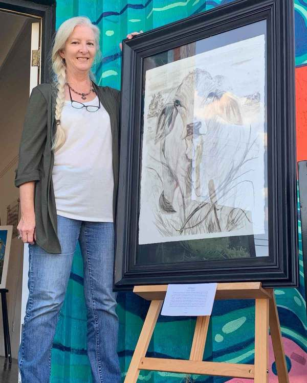 The framed painting of Whisper, with Madison Woods (the artist) for size context.